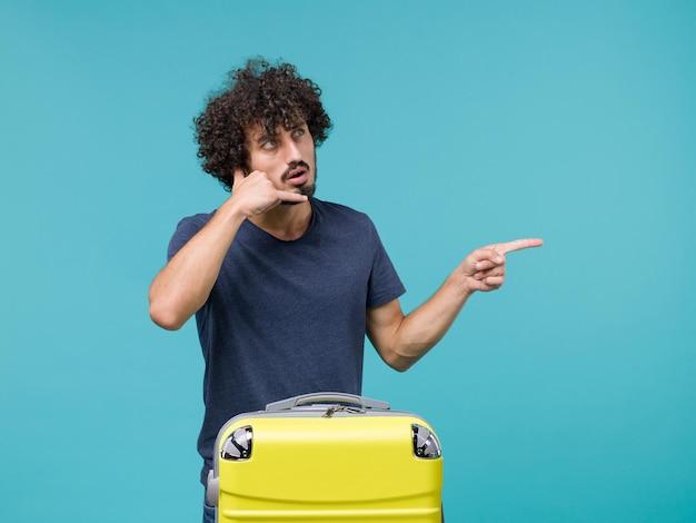 Homme en vacances en t-shirt bleu foncé posant sur bleu