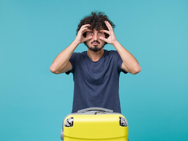 Homme en vacances en t-shirt bleu ouvrant largement les yeux sur le bleu
