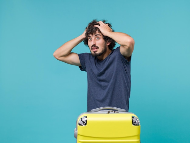 Homme en vacances en t-shirt bleu tenant sa tête sur bleu