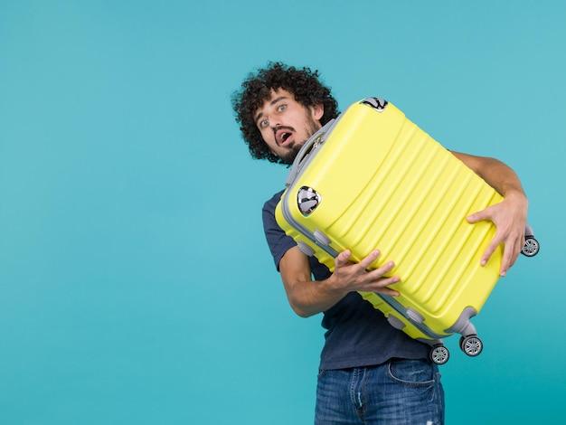 Homme en vacances tenant une grosse valise jaune sur bleu