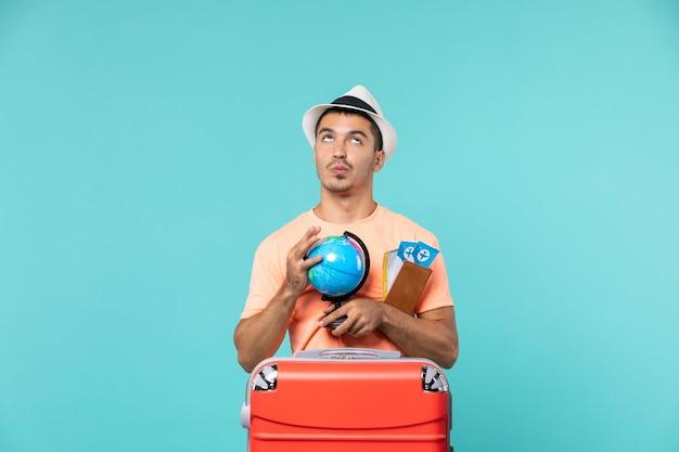 Homme en vacances tenant un petit globe avec des billets d'avion sur bleu