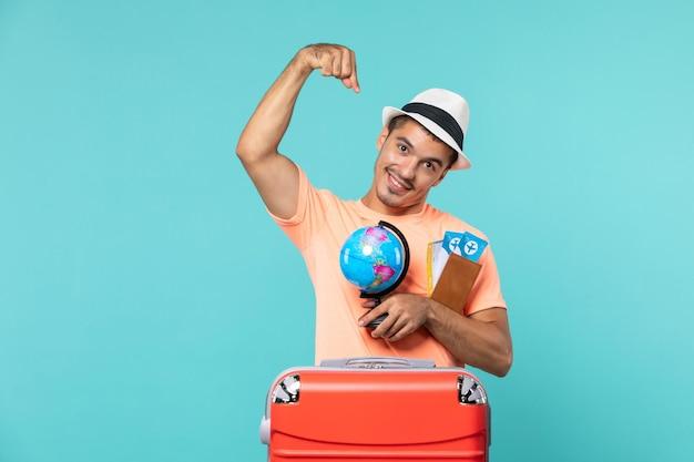 Homme en vacances tenant un petit globe et des billets sur bleu clair