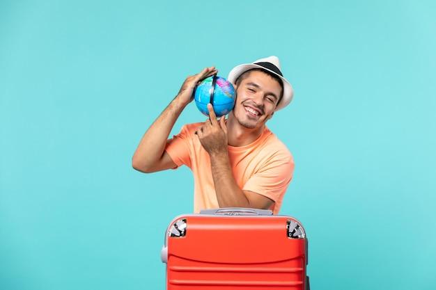 Homme en vacances tenant un petit globe sur bleu clair