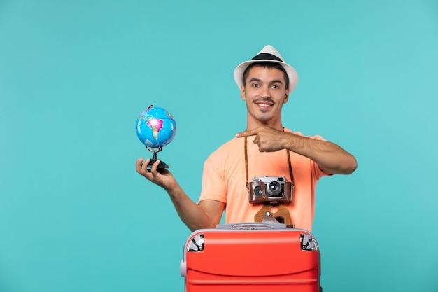 Homme en vacances tenant un petit globe sur bleu