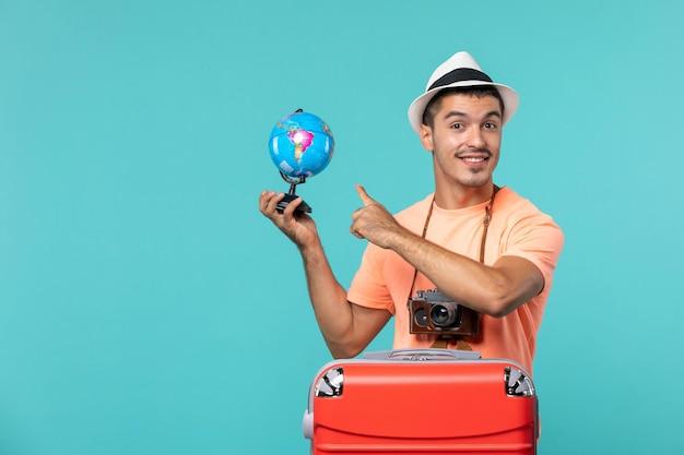 Homme en vacances tenant petit globe avec sourire sur bleu