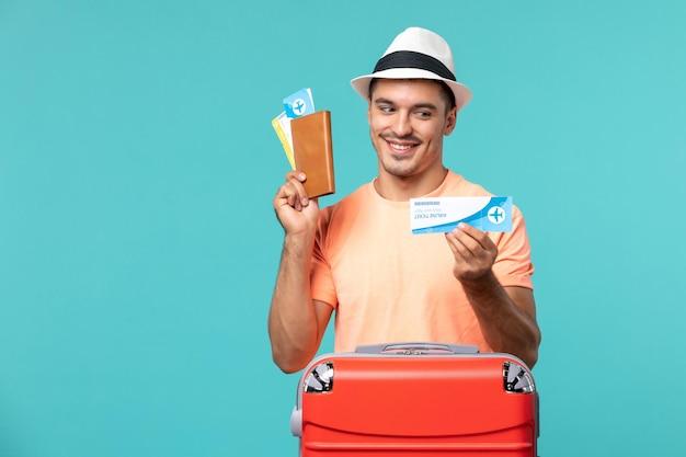 Homme en vacances tenant son billet sur bleu