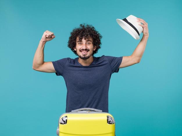 Homme en vacances tenant son chapeau sur bleu