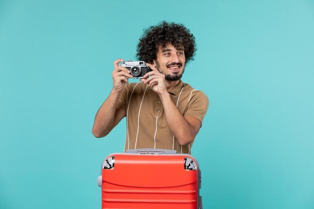 Homme en vacances avec valise rouge prenant des photos avec appareil photo sur bleu