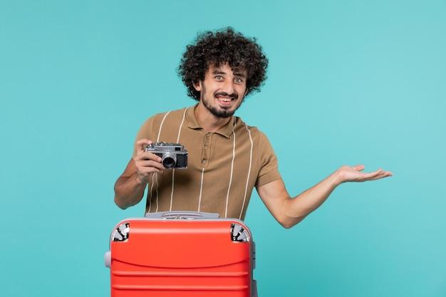 Homme en vacances avec une valise rouge prenant des photos avec un appareil photo souriant sur bleu