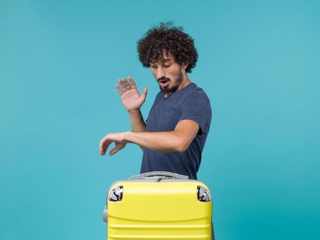 Homme en vacances vérifiant l'heure sur bleu