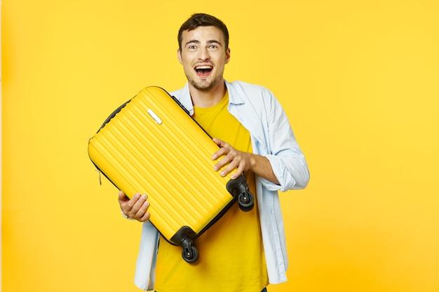 Homme avec valise jaune voyage vacances fond jaune