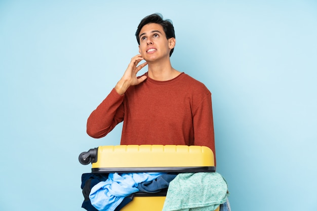 Homme avec une valise pleine de vêtements sur le mur bleu en pensant à une idée