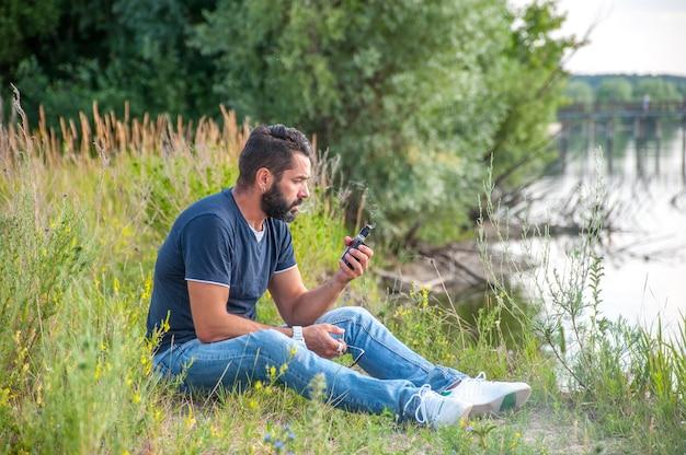 Homme de vape brutal élégant fumant une cigarette électronique sur l'herbe de la forêt