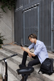 Homme avec vélo électrique dans la ville à l'aide de smartphone