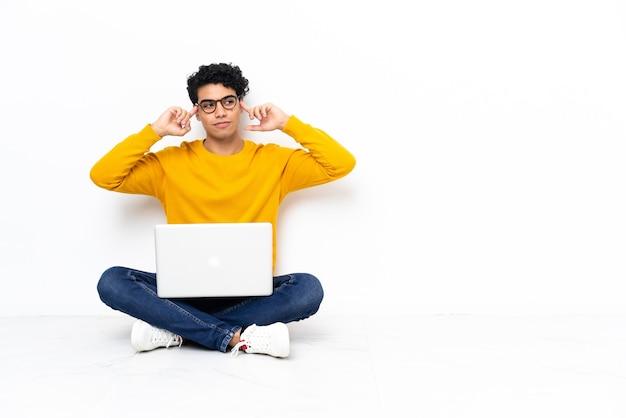 Homme vénézuélien assis sur le sol avec un ordinateur portable ayant des doutes et de la réflexion