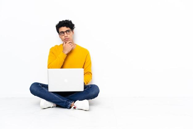 Homme vénézuélien assis sur le sol avec un ordinateur portable ayant des doutes