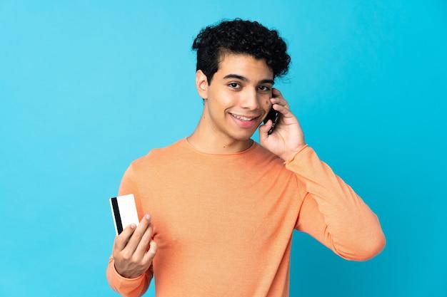 Homme vénézuélien isolé sur bleu en gardant une conversation avec le téléphone mobile et tenant une carte de crédit