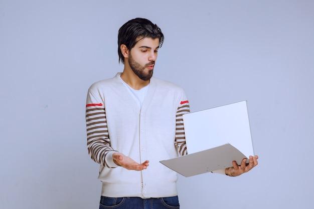 Homme vérifiant le dossier de rapport et essayant de comprendre ce qui y est écrit.