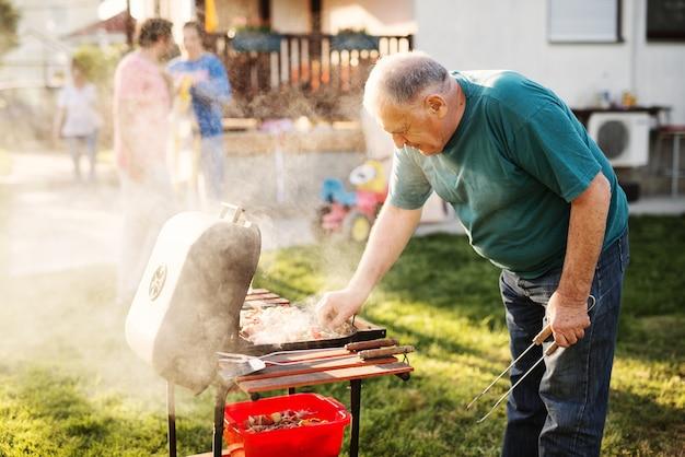 Homme vérifiant sur le grill dans son arrière-cour.