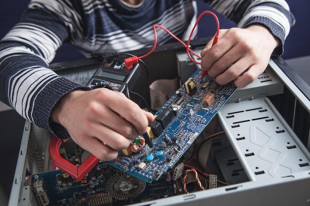 Homme vérifiant l'ordinateur avec un multimètre.