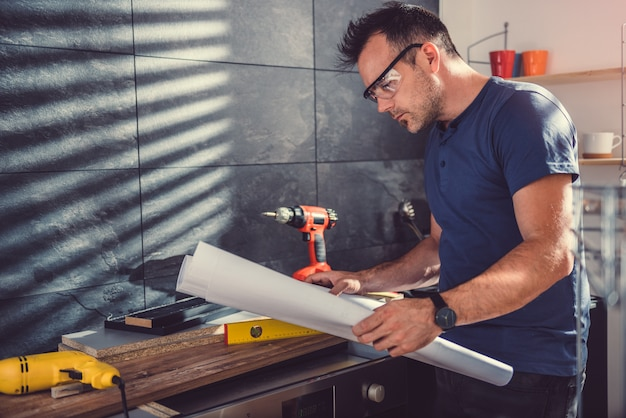 Homme vérifiant les plans lors de la construction d'armoires de cuisine