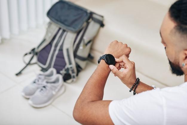 Homme vérifiant la smartwatch avant de commencer à emballer son sac à dos