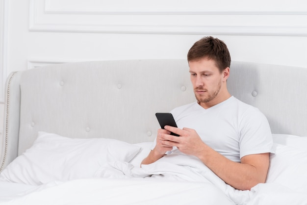 Homme vérifiant son téléphone après s'être réveillé avec copie espace