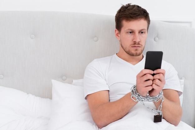 Homme vérifiant son téléphone après s'être réveillé