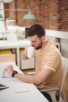 Homme vérifiant le temps tout en prenant un café