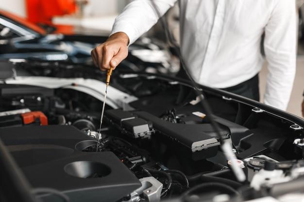 L'homme vérifie la présence d'huile dans la voiture. gros plan, main mâle