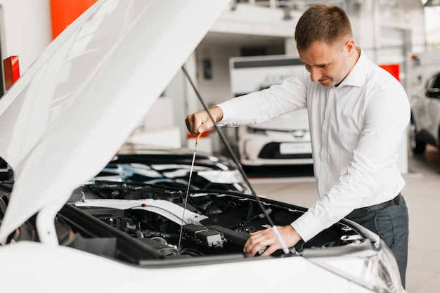 L'homme vérifie la présence d'huile dans la voiture en gros plan