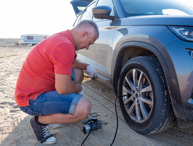 Un homme vérifie la pression des pneus. voyagez jusqu'à la mer en voiture.