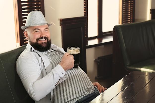 Homme avec verre de bière au pub