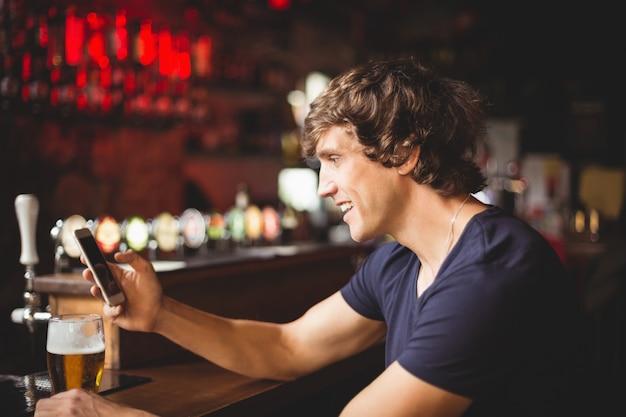 Homme, à, verre bière, utilisation, téléphone portable, dans, compteur
