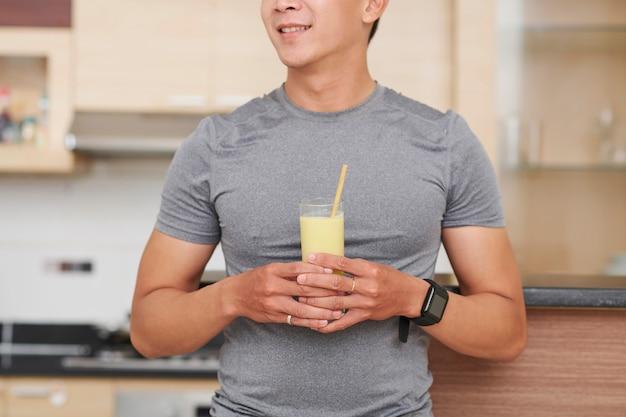Homme avec verre de cocktail protéint de banane