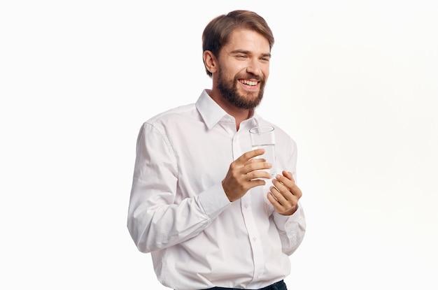 Homme avec verre d'eau chemise blanche lifestyle boisson fond clair