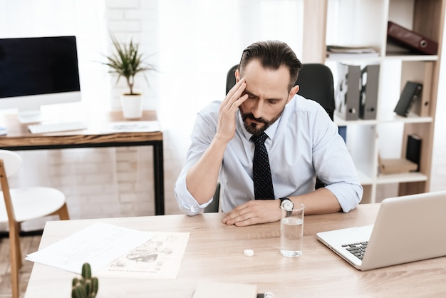 Homme avec un verre est assis à la table et tenant sa tête.
