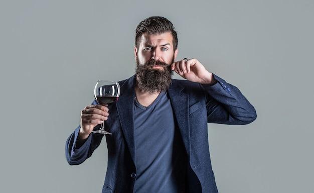 Homme avec un verre de vin rouge dans ses mains. homme barbu, barbu, sommelier dégustant du vin rouge. sommelier, dégustateur avec verre de vin, cave, vigneron masculin.