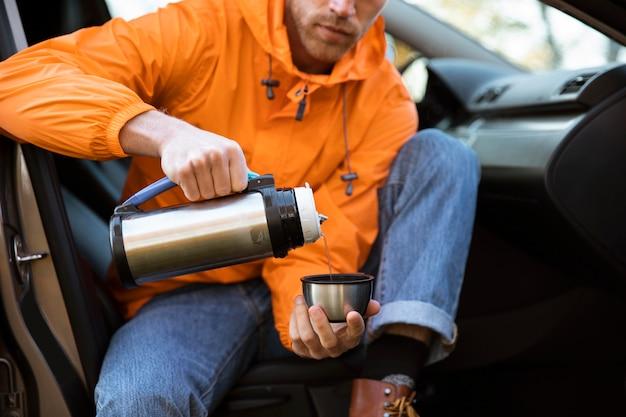 Homme versant une boisson chaude dans une tasse lors d'un voyage sur la route