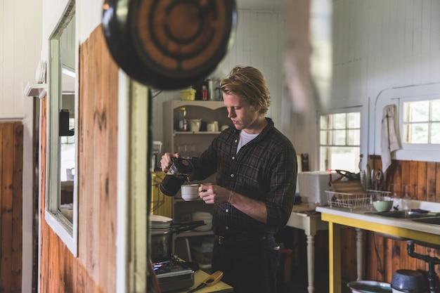 Homme versant du café dans la cuisine sur un vieux chalet en bois