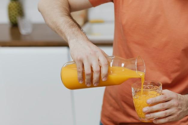 Homme versant du jus d'orange dans un verre
