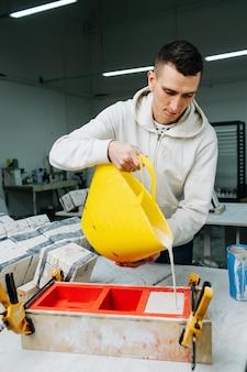 L'homme versant du plâtre de gypse sous forme ouverte pour le moulage de moules pour la fabrication de vaisselle