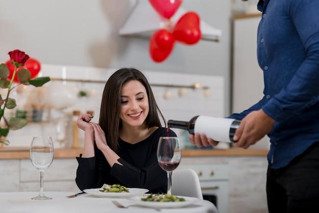 Homme versant du vin dans un verre pour sa petite amie