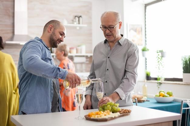 Homme versant du vin à son père dans la cuisine pendant le déjeuner en famille.