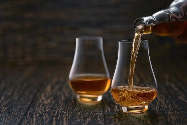 Homme versant du whisky dans des verres sur une table en bois rustique mise au point sélective.