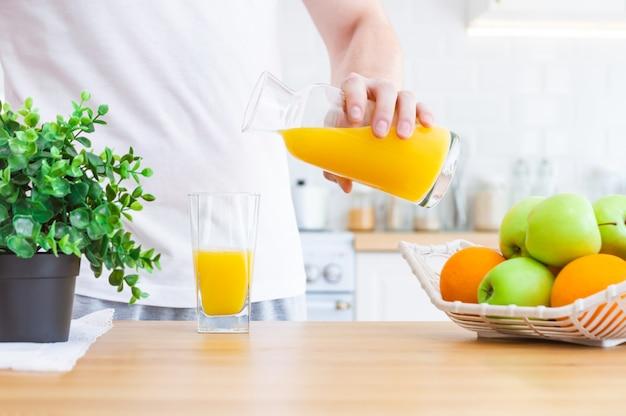 Homme versant le jus d'orange de la cruche dans un verre dans la cuisine.