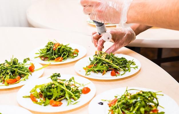 Homme versant de la sauce dans une assiette avec des ingrédients de la salade