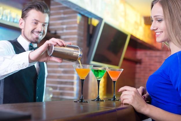 Un homme verse un cocktail à une belle fille.