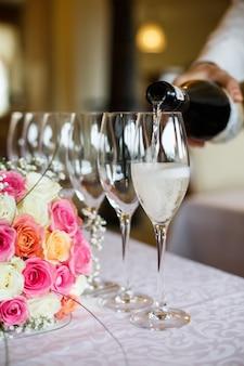 Homme verse du champagne dans les verres debout devant un bouquet de mariage sur la table