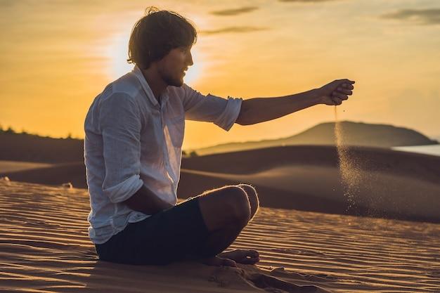 Un homme verse du sable dans le désert. poncez entre les doigts du concept.